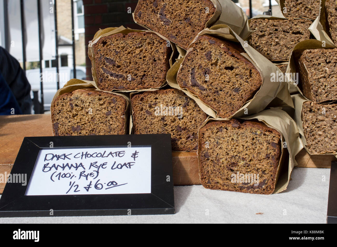 Dark chocolate and banana rye loaf breads in an outdoor market in London - Stock Image