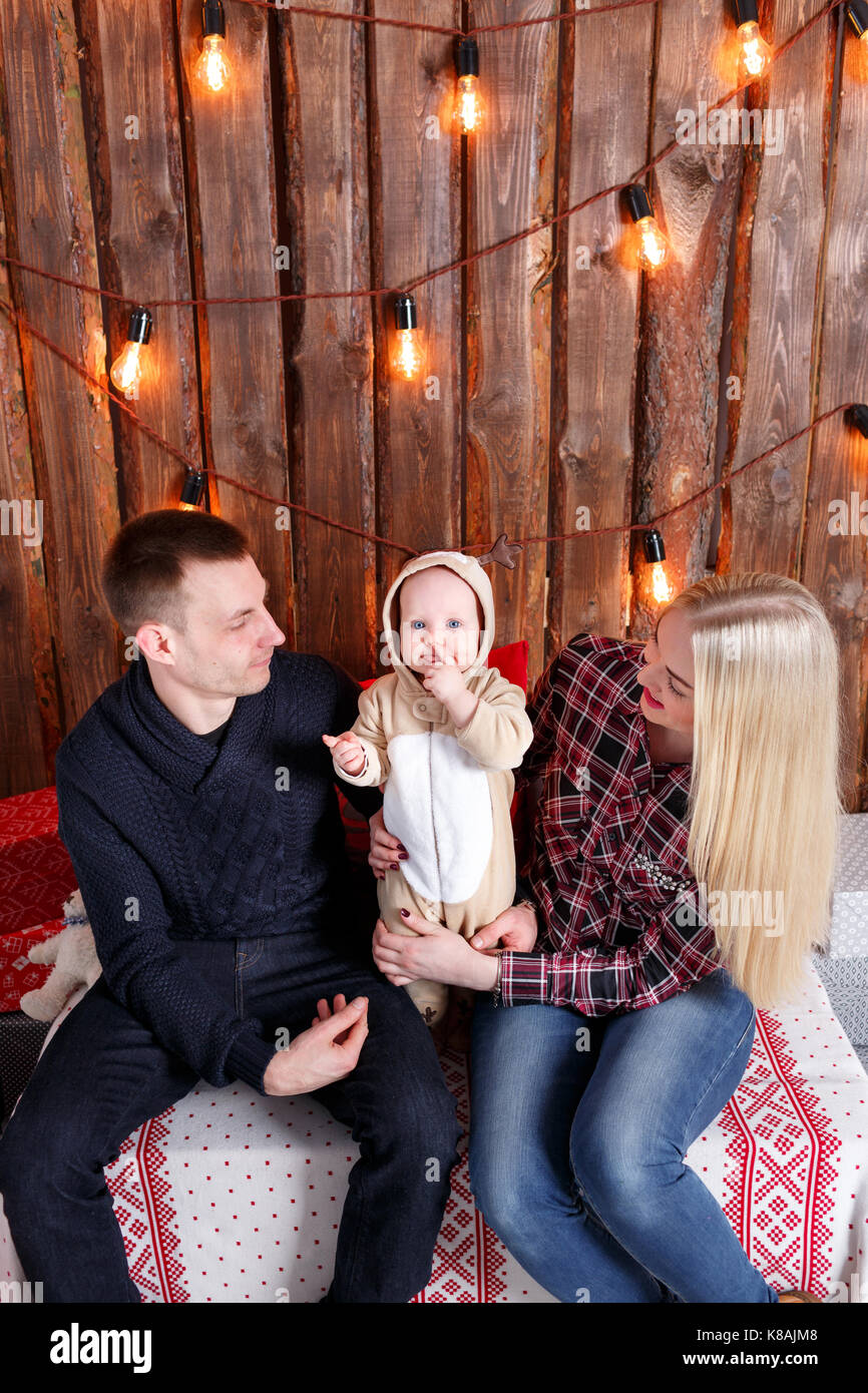 Happy family at Christmas. The parents and the baby sitting. Wall of wooden planks and garland - Stock Image