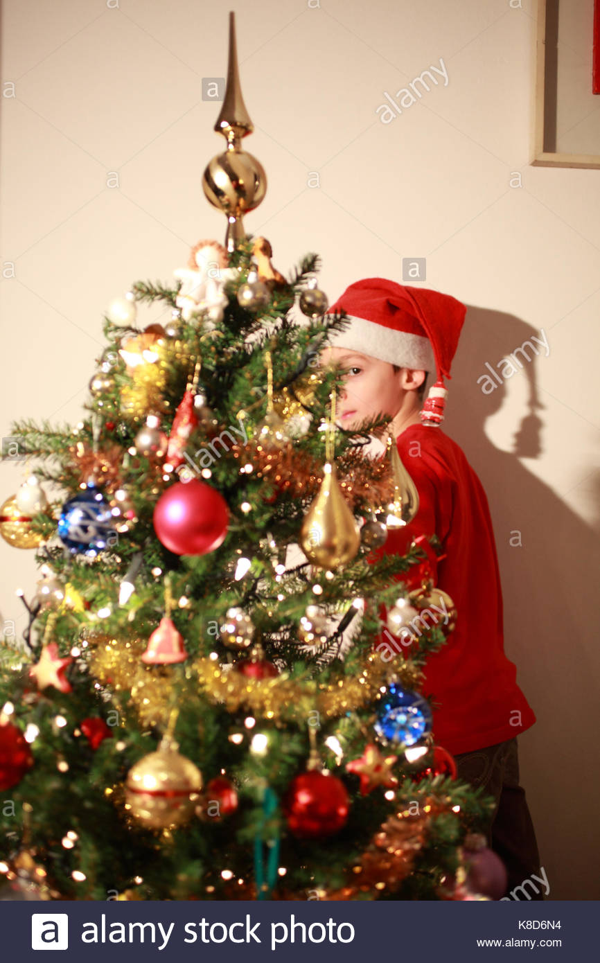 a child wearing Santa Claus hat in a room with a Chrismast tree - Stock Image