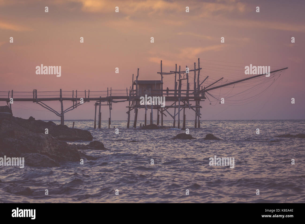 Nostalgic evening at Adriatic sea. Lonely womant stands at trabocchi pier - Stock Image