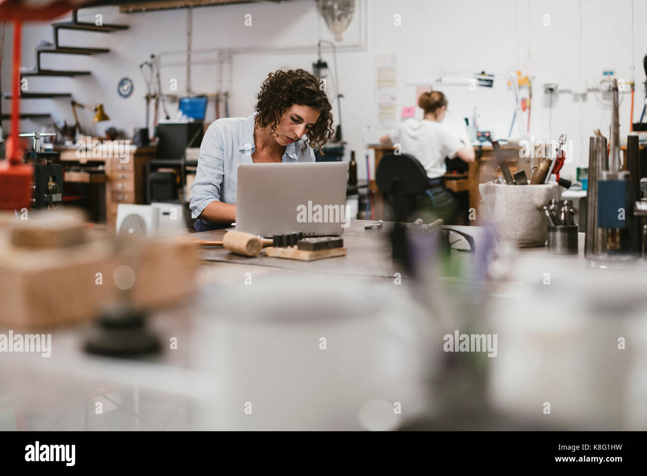 Female jeweller typing on laptop at workbench - Stock Image