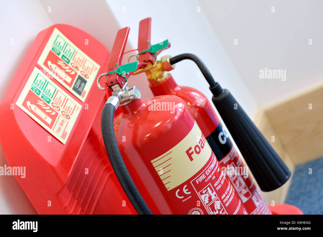 two fire extinguishers on a specially designed holder on the wall in an office building. Foam and Carbon dioxide - Stock Image