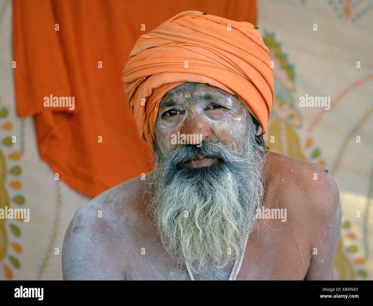 Old Indian Hindu sadhu with orange turban and sacred white ash (vibhuti) all over his face and beard - Stock Image