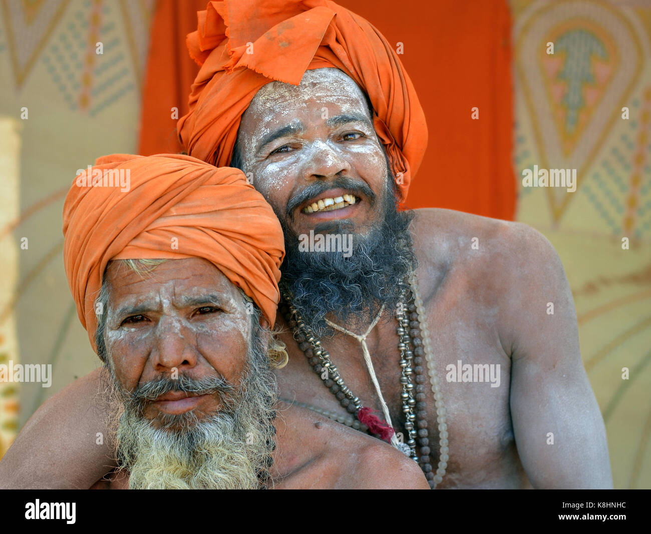 Two happy Indian Hindu sadhus with orange turbans and sacred white ash all over their faces, beards and bodies, - Stock Image