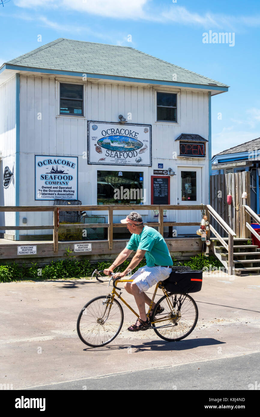 Outer Banks North Carolina NC Ocracoke Island Ocracoke Seafood Company fishmonger exterior man riding pedaling bicycle - Stock Image