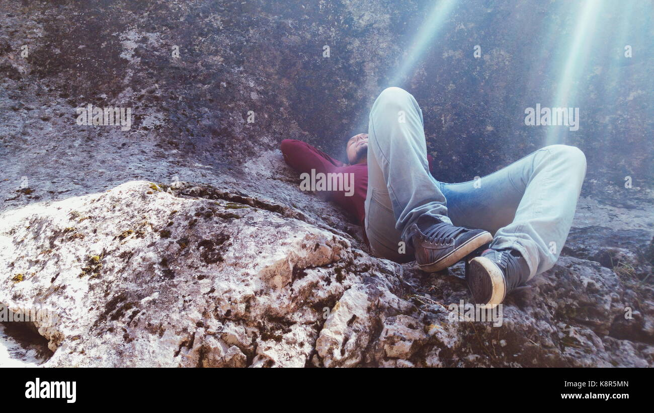 Young man sleeping in a mountain - Stock Image