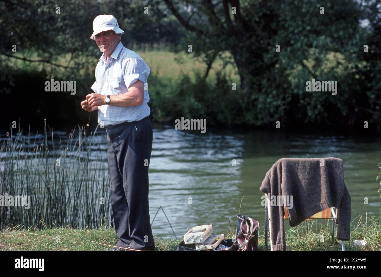 elderly man on a river bank fishing and smiling enjoying himself - Stock Image