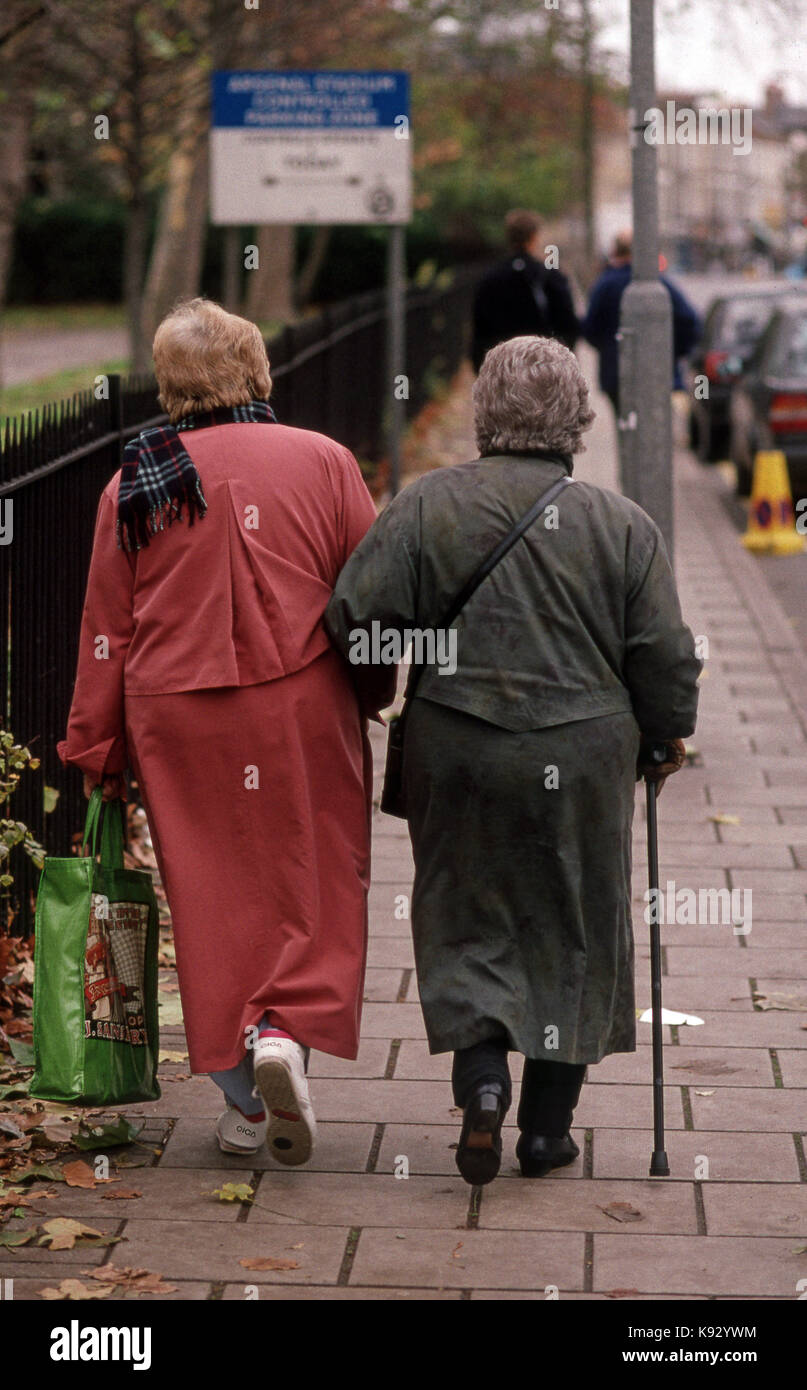 back view of elderly women walking arm in arm one holding shopping bag and the other using a walking stick - Stock Image
