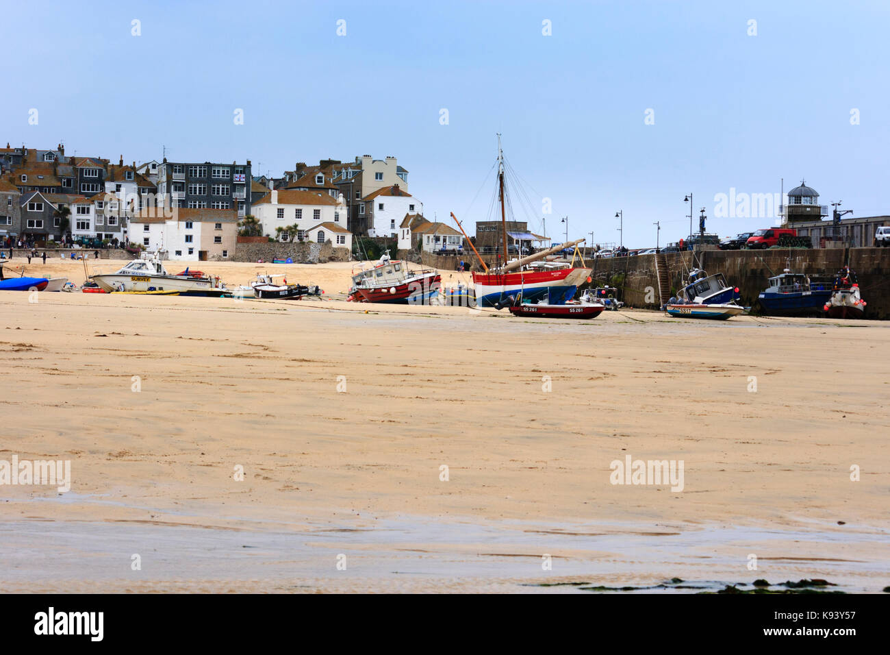Fishing and pleasure boats beached on the strand at St Ives, Cornwall, at low tide - Stock Image