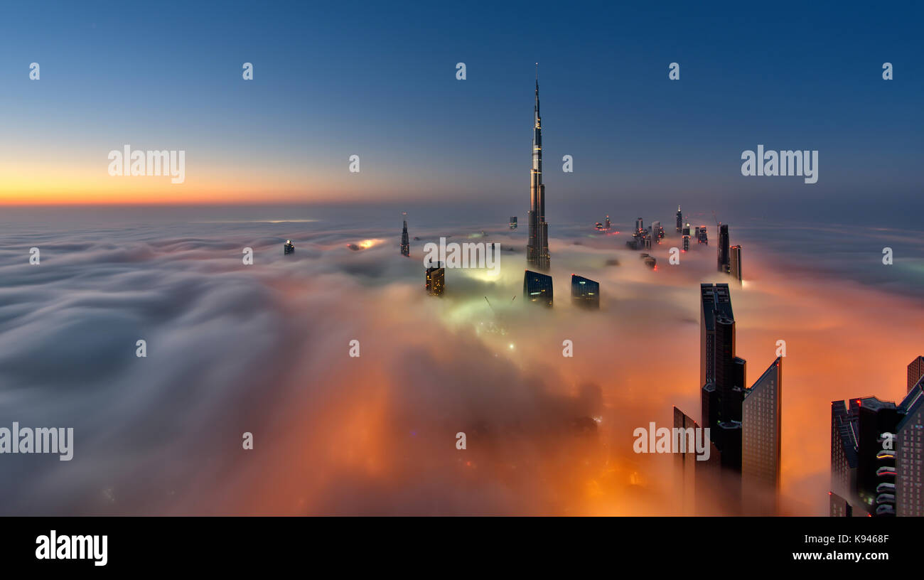 View of the Burj Khalifa and other skyscrapers above the clouds in Dubai, United Arab Emirates. - Stock Image