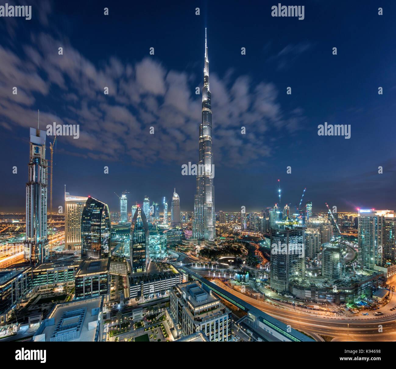 Cityscape of Dubai, United Arab Emirates at dusk, with the Burj Khalifa skyscraper and illuminated buildings in - Stock Image
