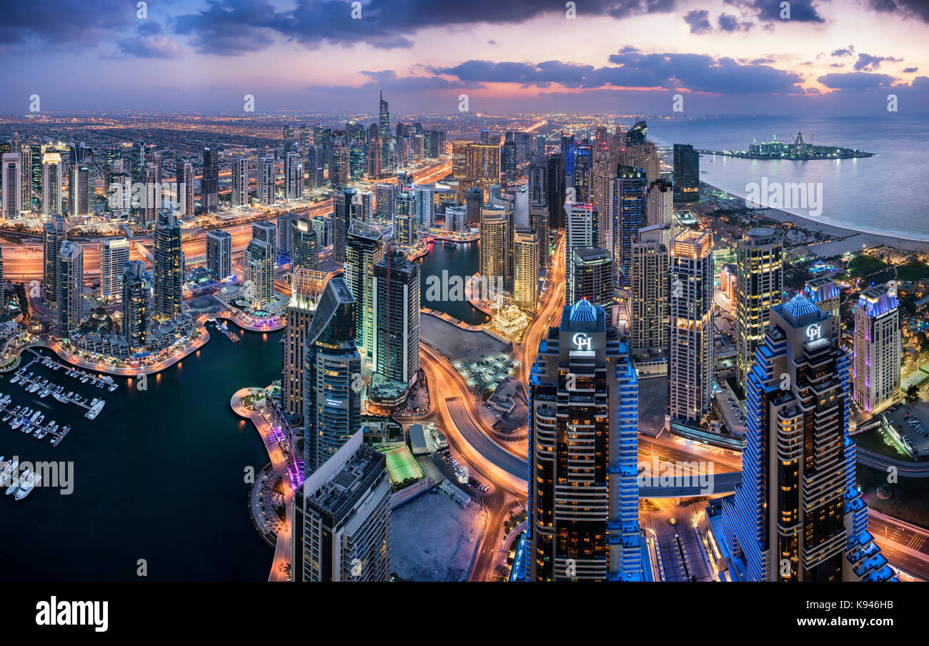 Aerial view of the cityscape of Dubai, United Arab Emirates at dusk, with illuminated skyscrapers and the marina - Stock Image
