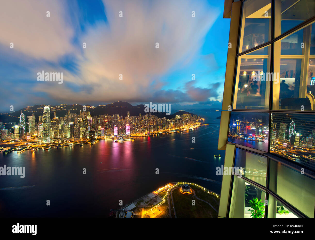Aerial view of Hong Kong cityscape with illuminated skyscrapers at dusk. - Stock Image