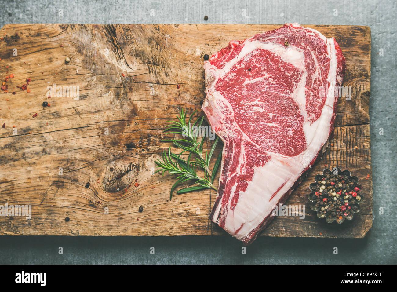 Raw uncooked beef steak rib-eye on board, copy space - Stock Image