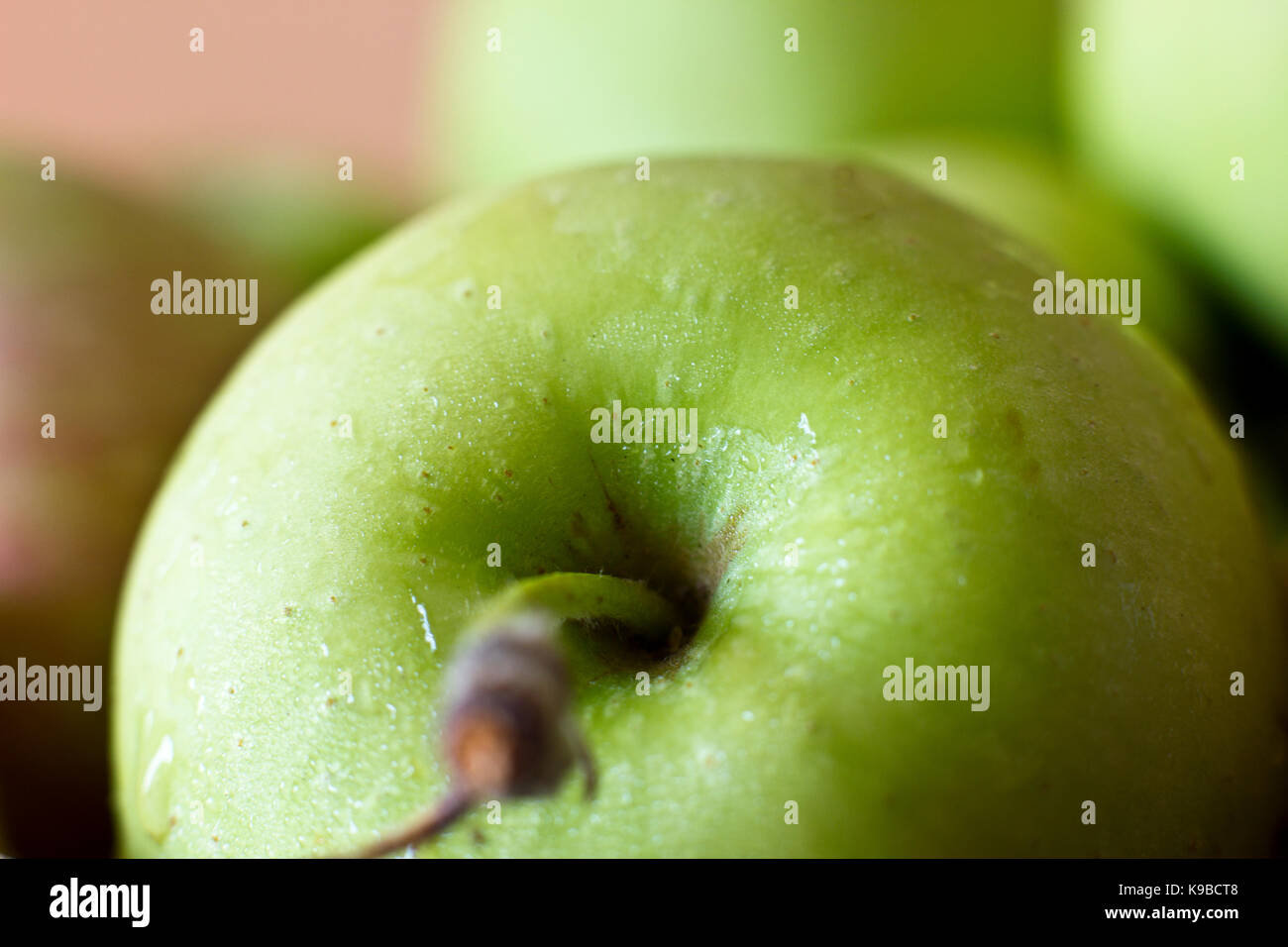 A green apple in the drops of water. Macro shooting. Selective focus. - Stock Image