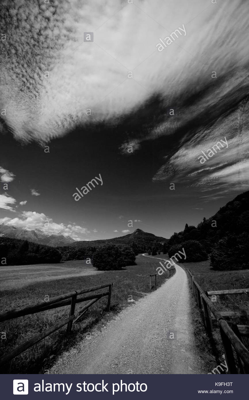 Landscape: Black and white image of a windy road in the mountains - Stock Image