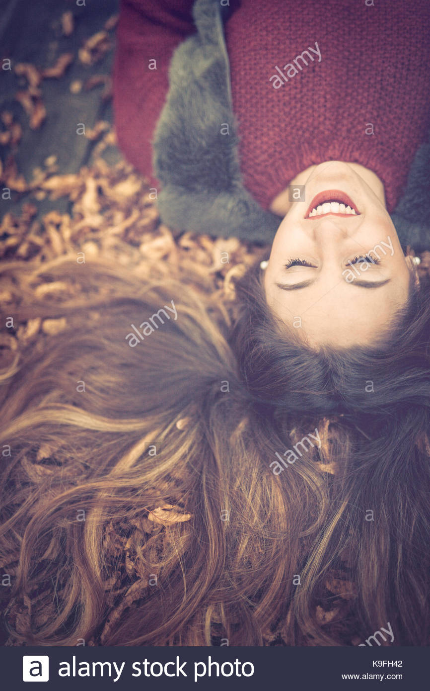 Girl smiling on a bed of leaves - Stock Image