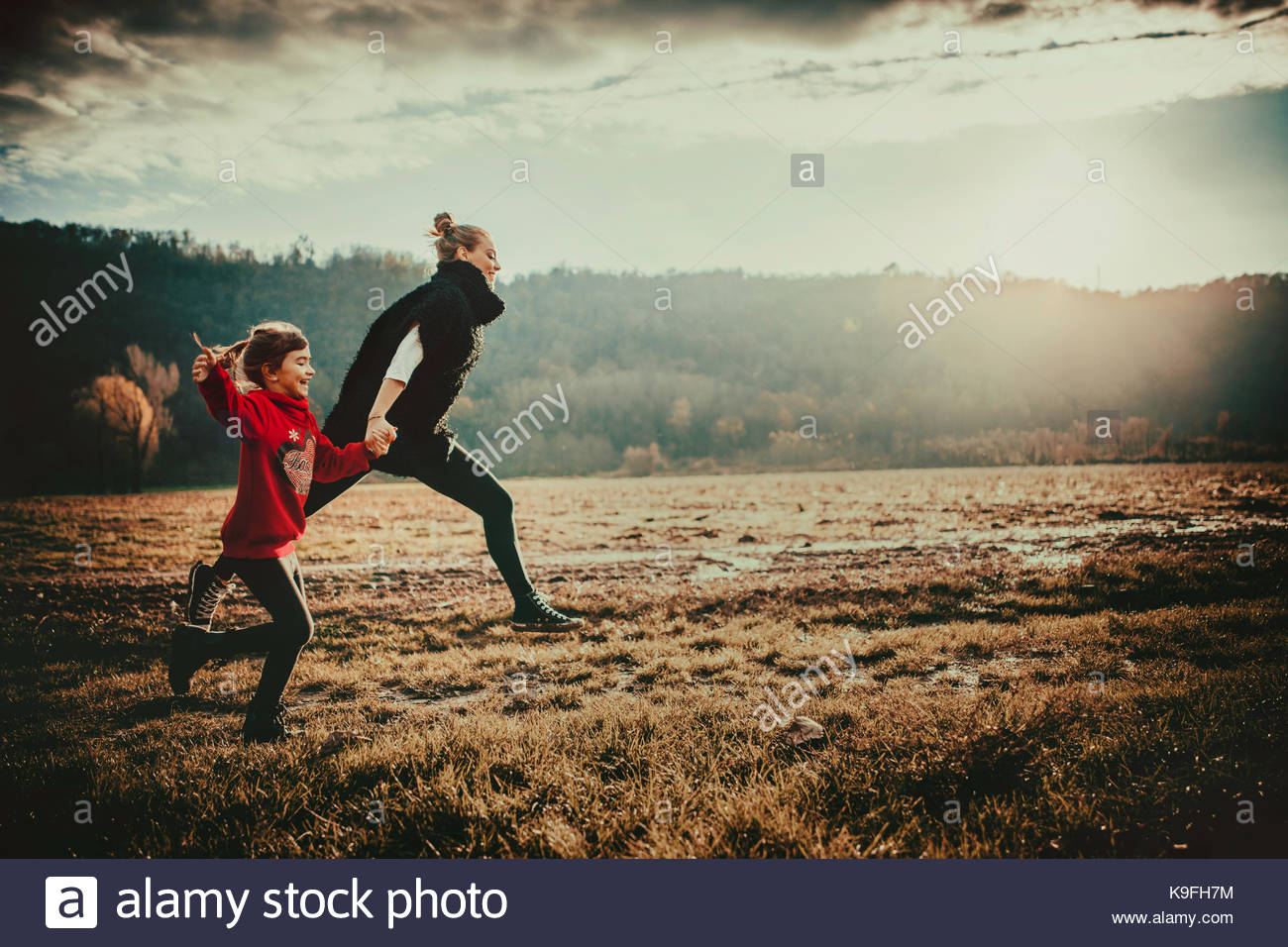 Freedom, carelessness, girls running in fields in the countryside at sunset - Stock Image