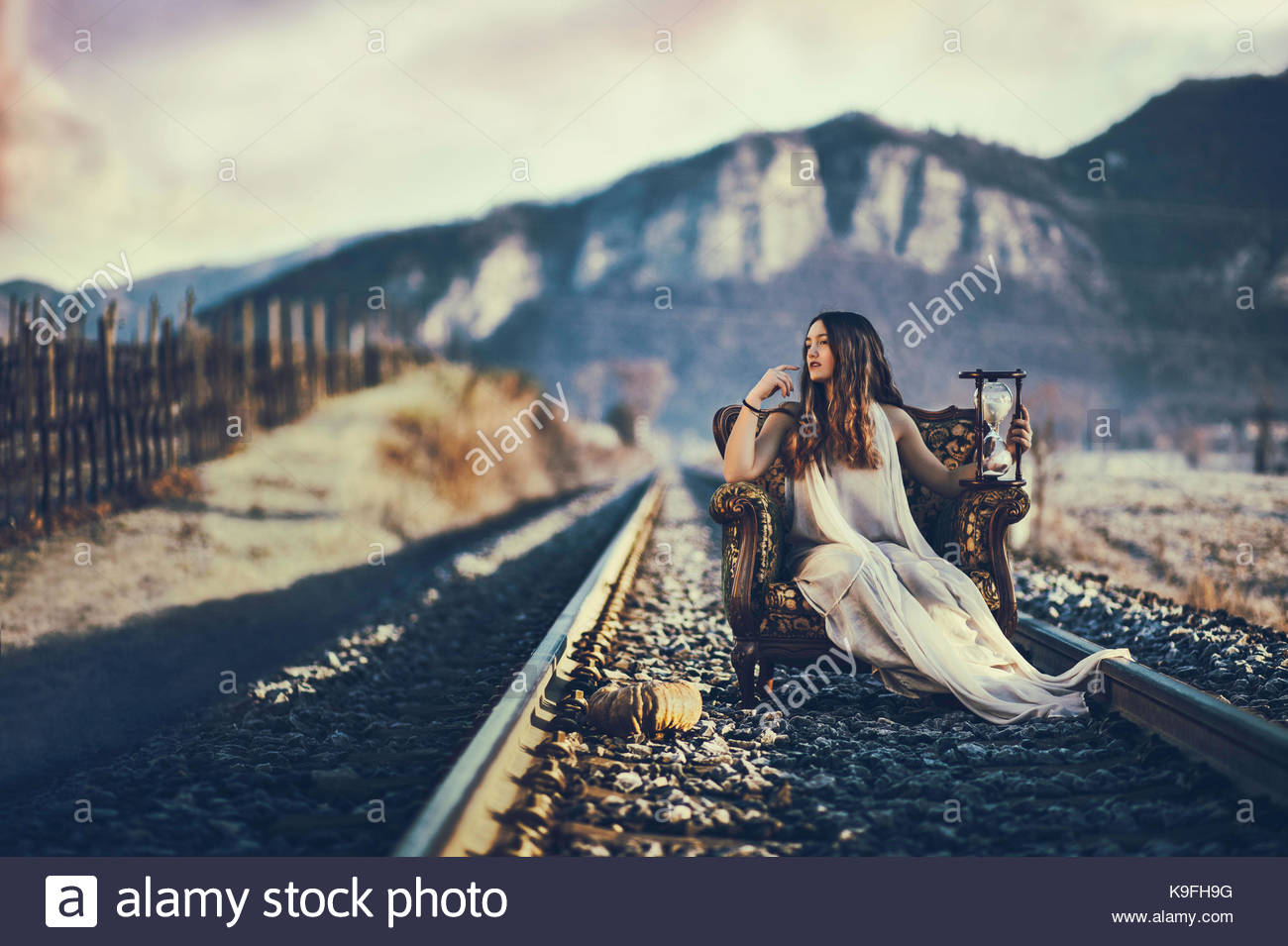 Girl sitting on an armchair on a railway, holding an hourglass - Stock Image