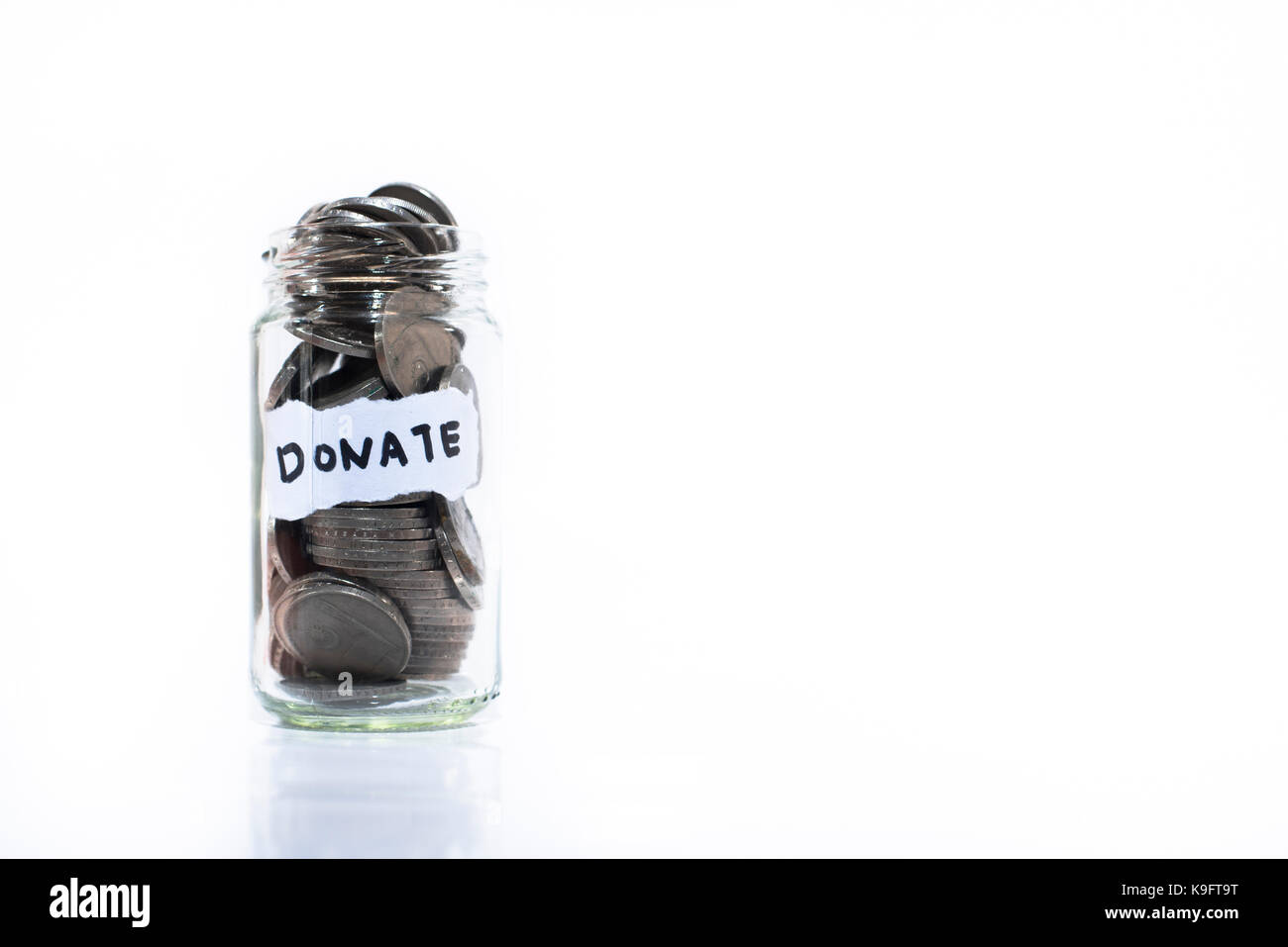 Coins in glass jar with a note written ' DONATE '. Isolated on a white background. Saving money to help - Stock Image
