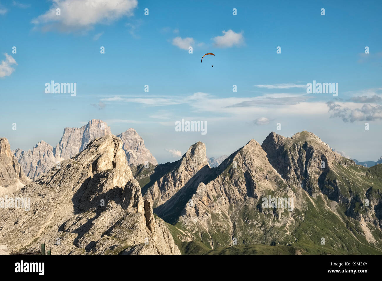 The Dolomites, Northern Italy. A paraglider soars above the tower of Ra Gusela (2595m), seen from the mountain guesthouse - Stock Image