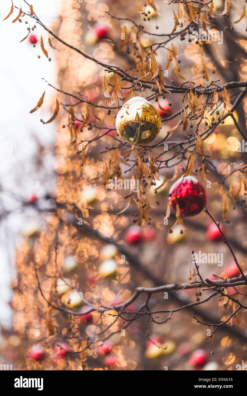 Streets fully decorated for Christmas with red and gold balls. Christmas tree in the city. House illuminated with - Stock Image