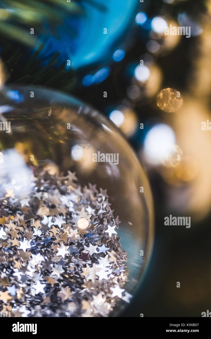 Christmas ball close-up with a lot small shiny stars inside - Stock Image