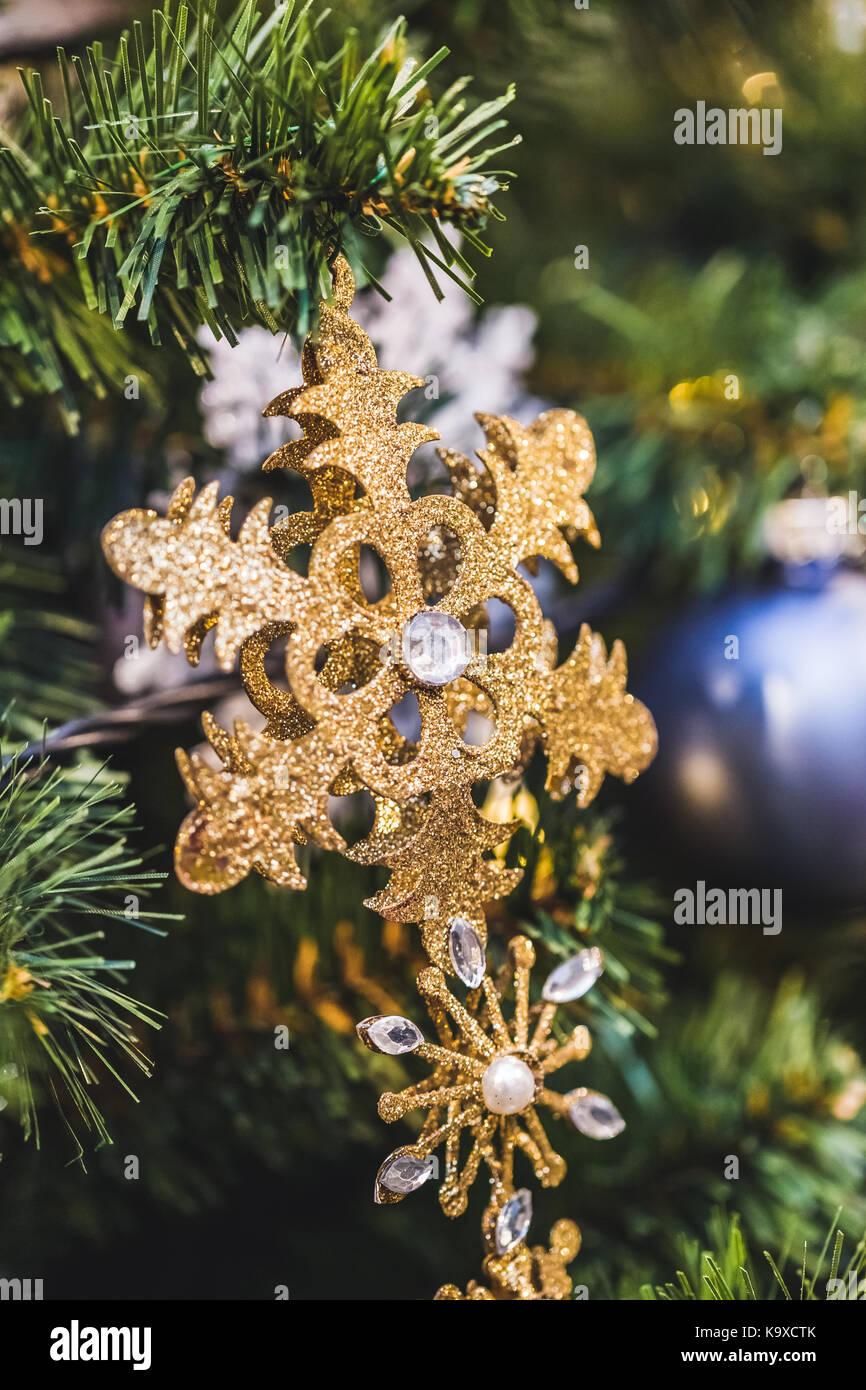 Gold flashing snowflake with diamond close-up as Christmas tree decor - Stock Image