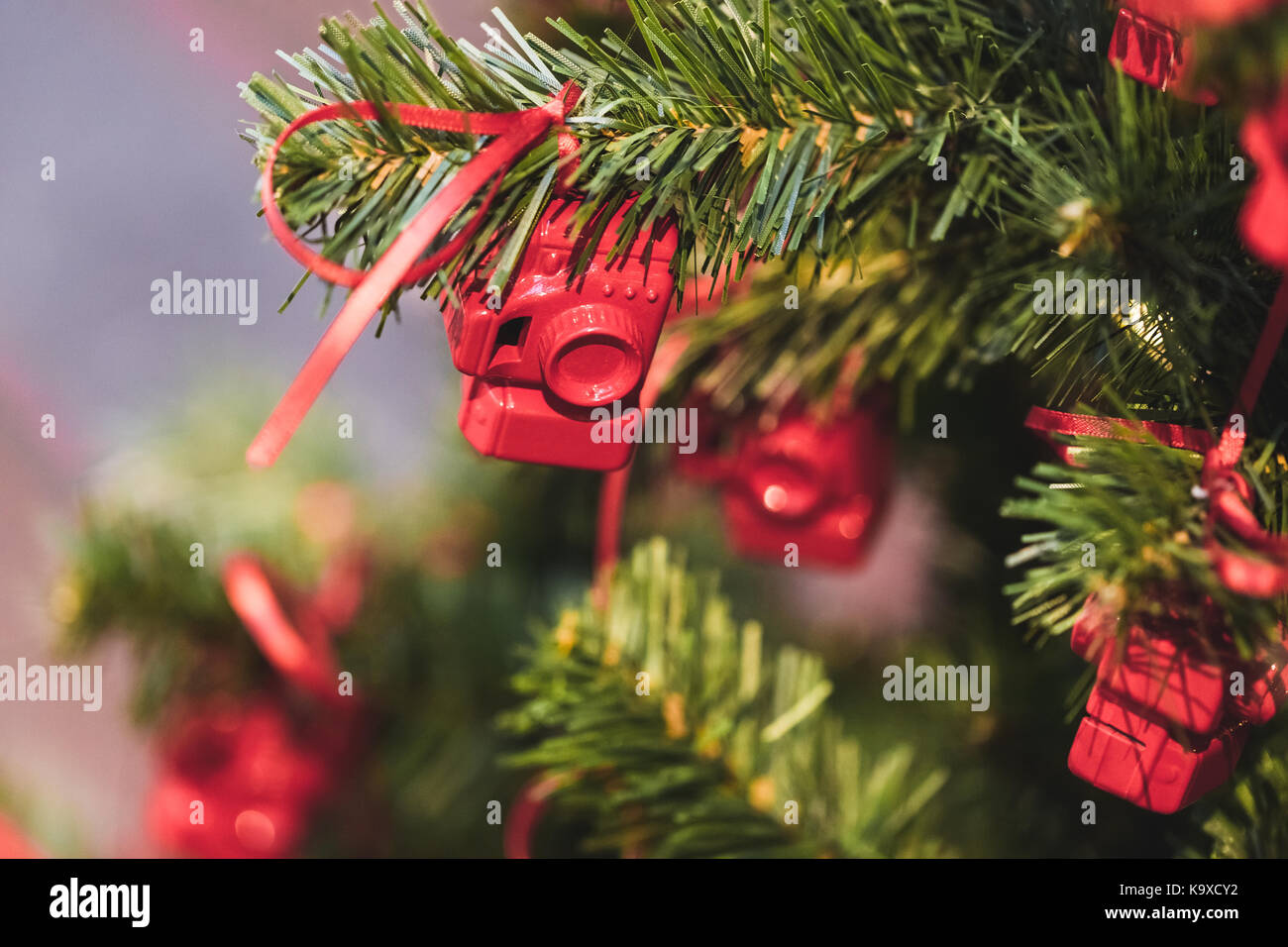 Christmas tree decorated with small figures of red photo cameras - Stock Image