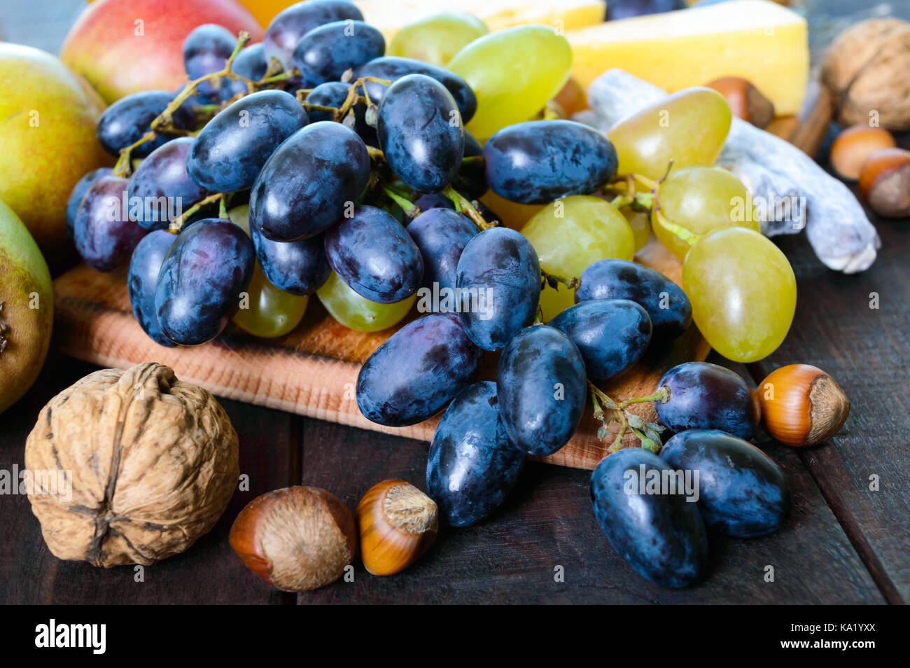 Autumn set of products: grapes, walnuts, hazelnuts, plums, honey, cheese, raisins, pears, dried cranberries on a - Stock Image