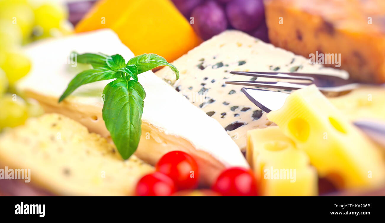 Closeup photo of a tasty cheese assorted, blue cheese, brie, camembert, cheddar, gouda, luxury French cheese, delicious - Stock Image