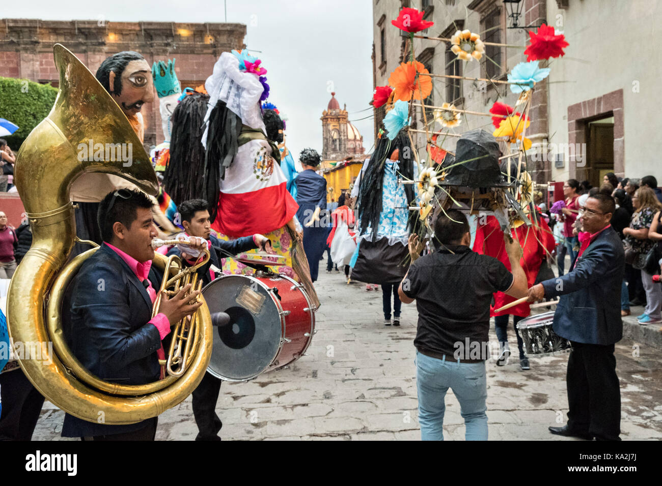 A marching band follows a parade of giant paper-mache puppets called mojigangas in a procession through the city Stock Photo