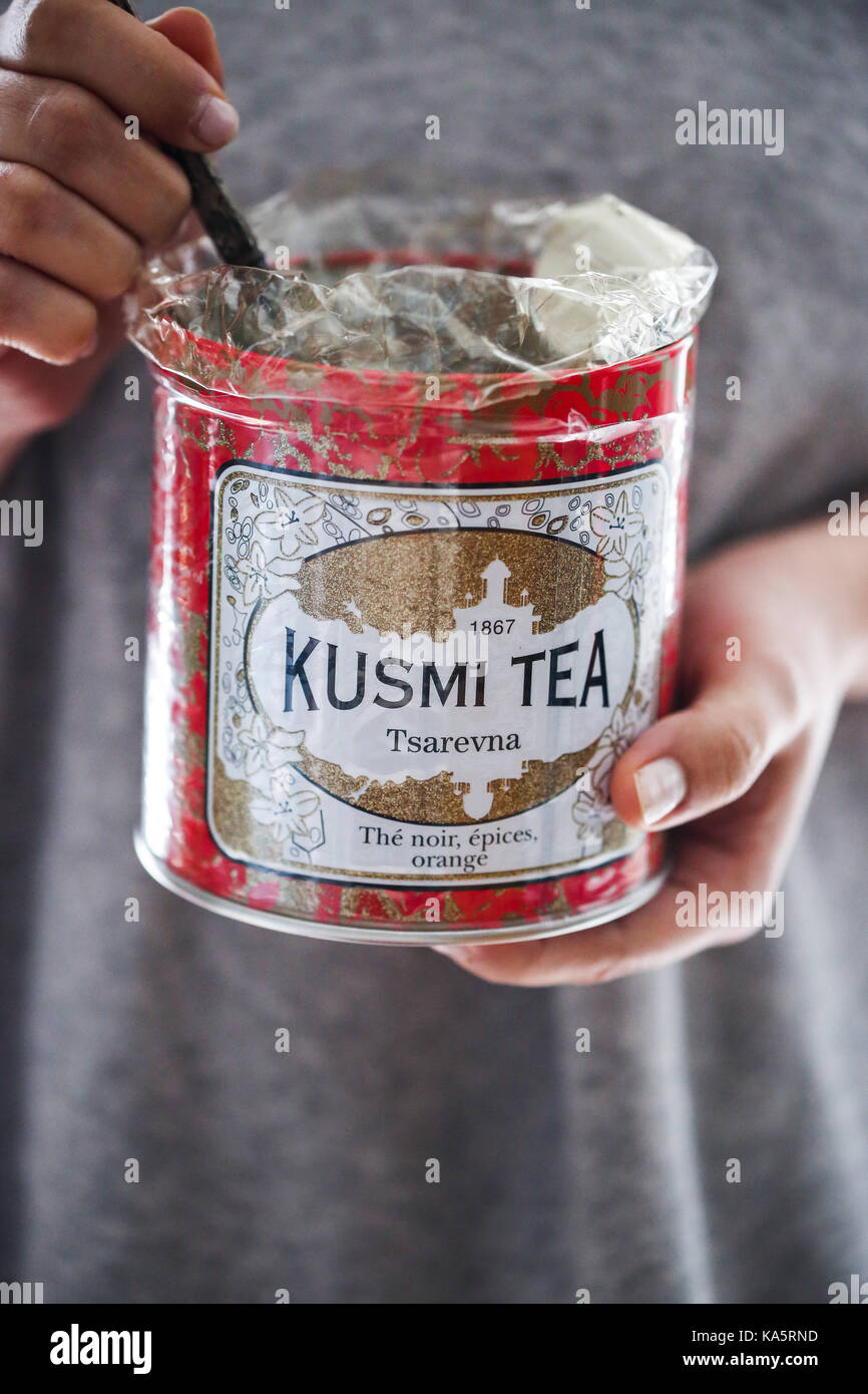 A woman holds a Kusmi tea tin can in her hands. - Stock Image