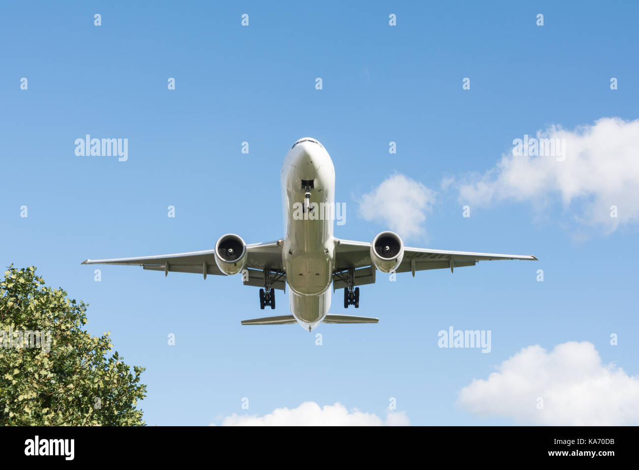 A low flying jet aircraft descending towards Heathrow Airport, Terminal 4, in Hounslow, Middlesex, UK. - Stock Image