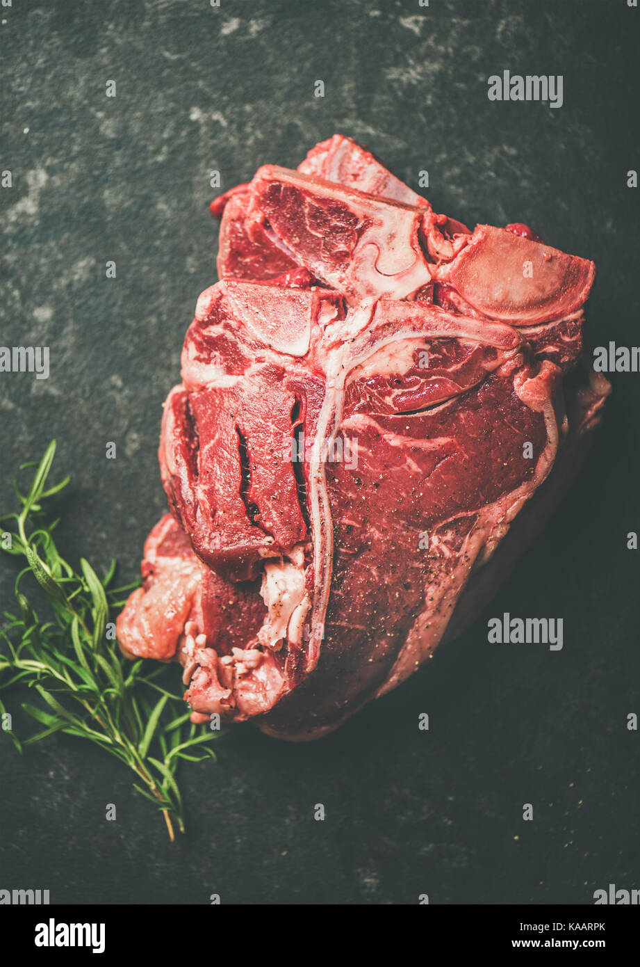 Fresh raw beef meat t-bone steaks with rosemary, black background - Stock Image