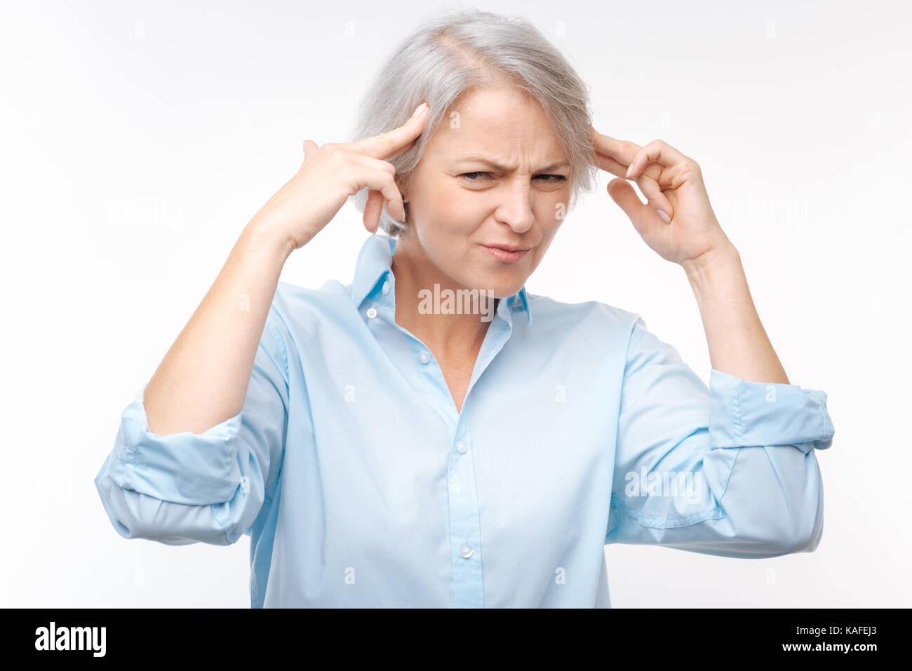 Irritated grey-haired woman pressing fingers to temples - Stock Image