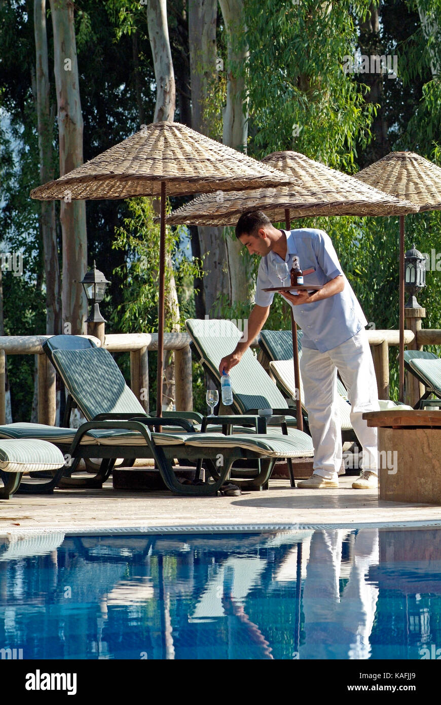 waiter collecting empties beside swimming pool akyaka turkey - Stock Image