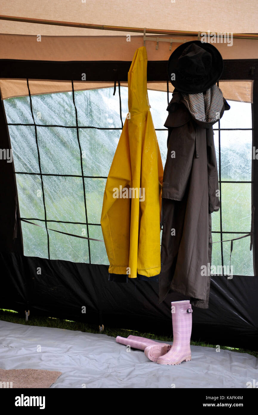 wet weather clothing and footwear hung up to dry in caravan awning - Stock Image