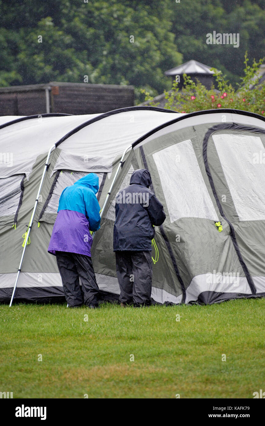 older couple erecting tent in wet weather - Stock Image