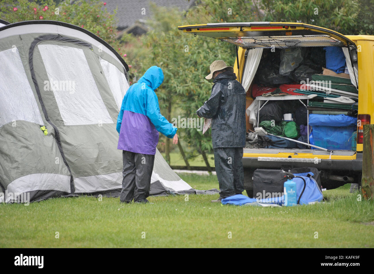 older couple pitching tent in the rain - Stock Image