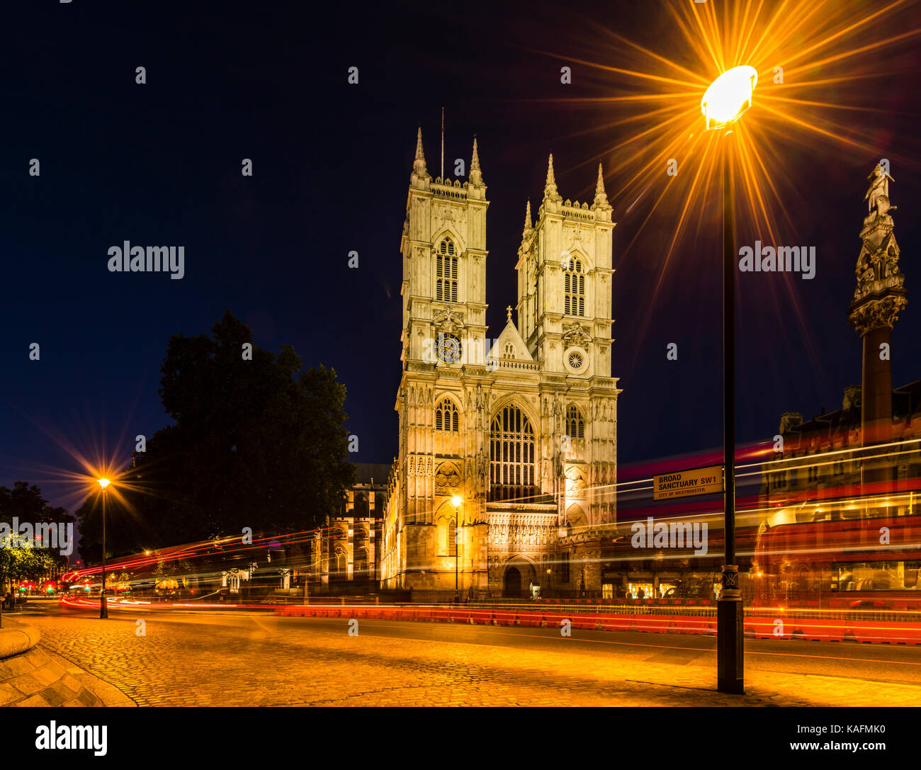 Red London buses in front of Westminster Abbey at night, London, UK - Stock Image