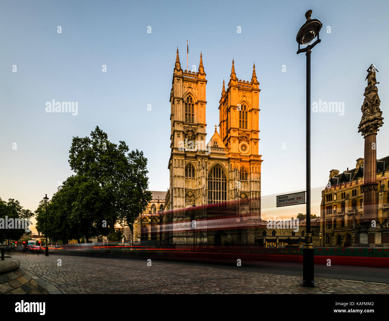 Red London buses in front of Westminster Abbey at dusk, London, UK - Stock Image