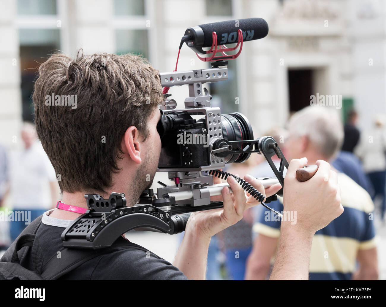 Man making video with DSLR camera supported on shoulder support - Stock Image