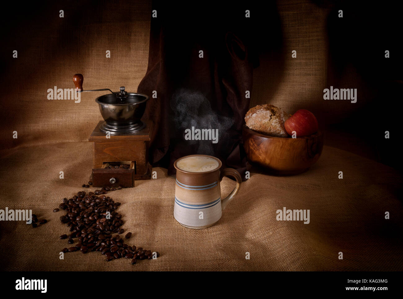 Steaming hot drink of coffee in a mug beside coffee grinder and coffee beans - Stock Image