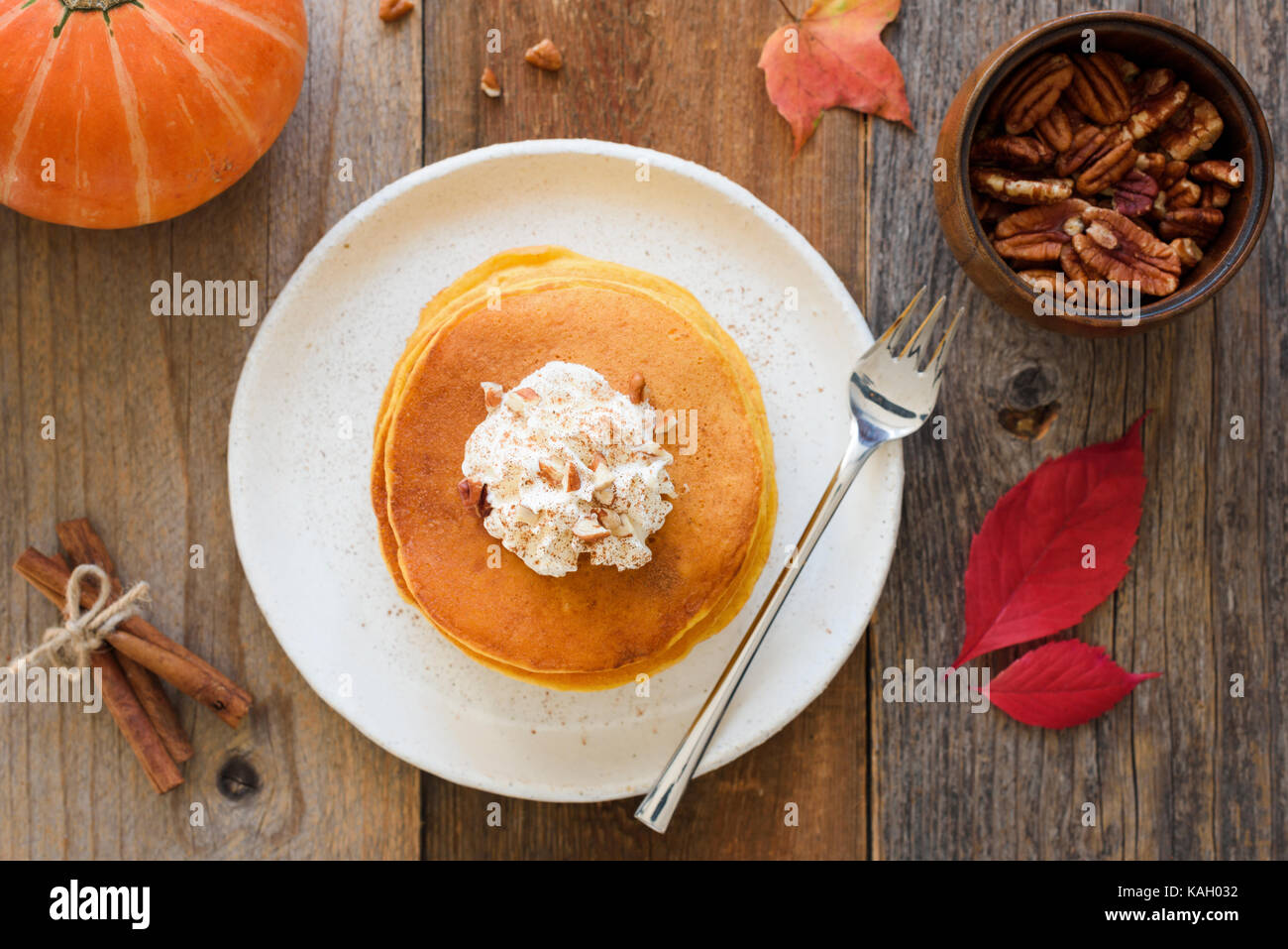 Pumpkin pancakes with whipped cream and cinnamon on wooden table. Top view, horizontal - Stock Image