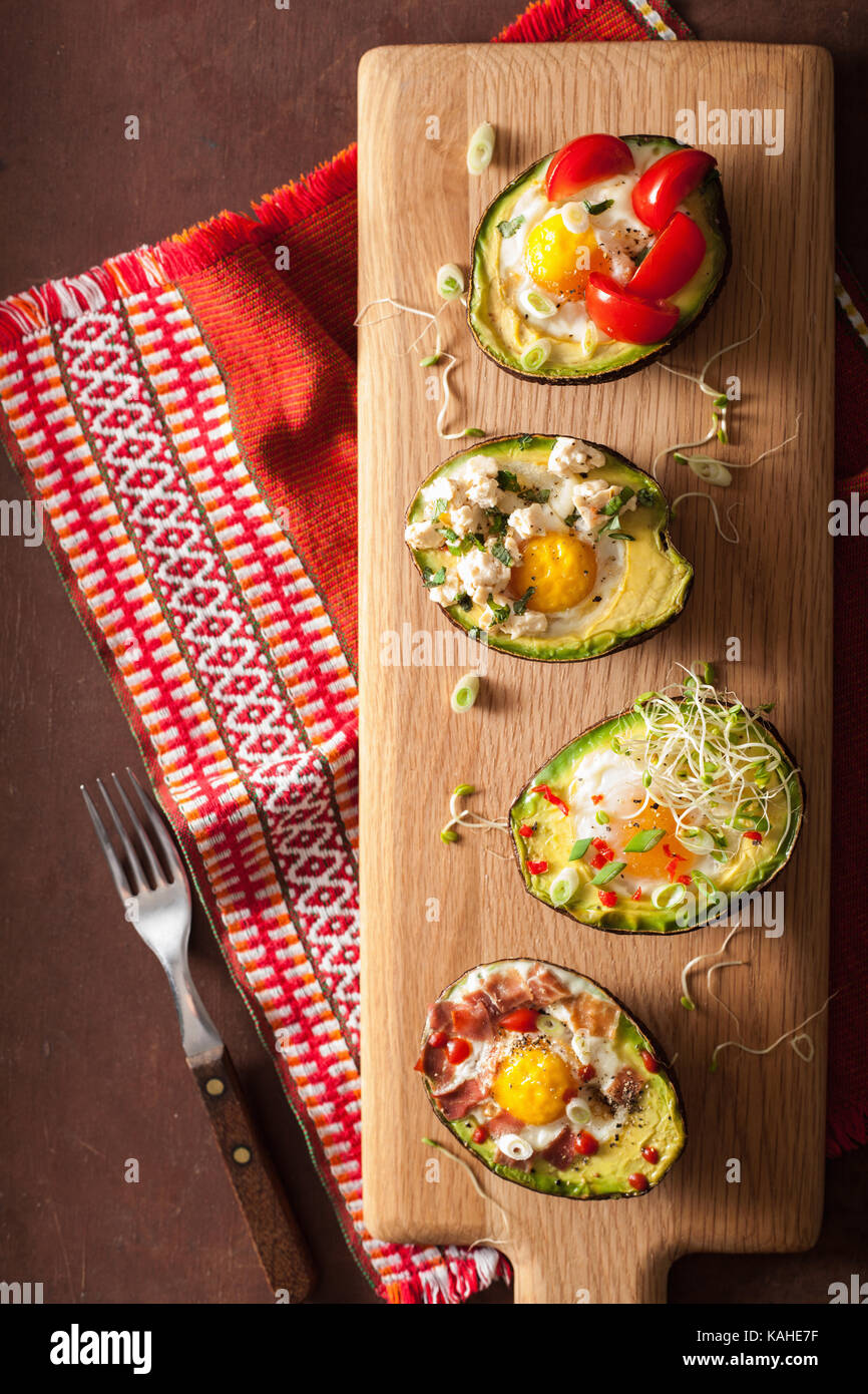 eggs baked in avocado with bacon, cheese, tomato and alfalfa sprouts - Stock Image