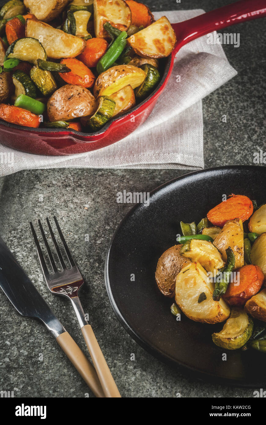 Plate and Skillet with  fried seasonal autumn vegetables (zucchini, potatoes, carrots, beans), on black stone table - Stock Image