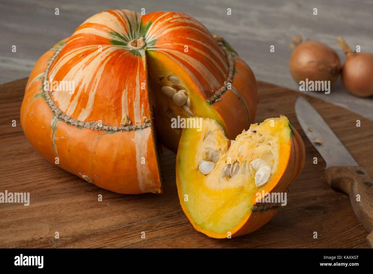 Fresh heirloom orange Turban squash and slice - Stock Image
