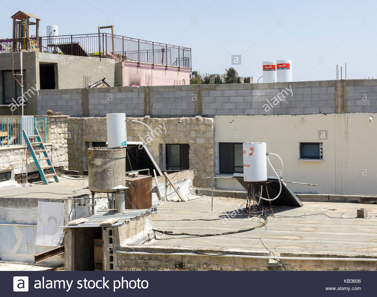 Standard Israeli passive-solar water heaters, seen on rooftops in the city of Safed, Northern District, Israel - Stock Image