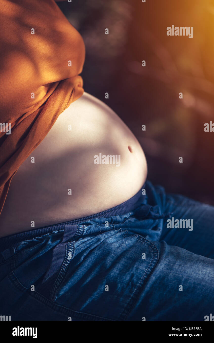 Pregnant woman relaxing and sunbathing belly on warm summer sunlight, selective focus - Stock Image